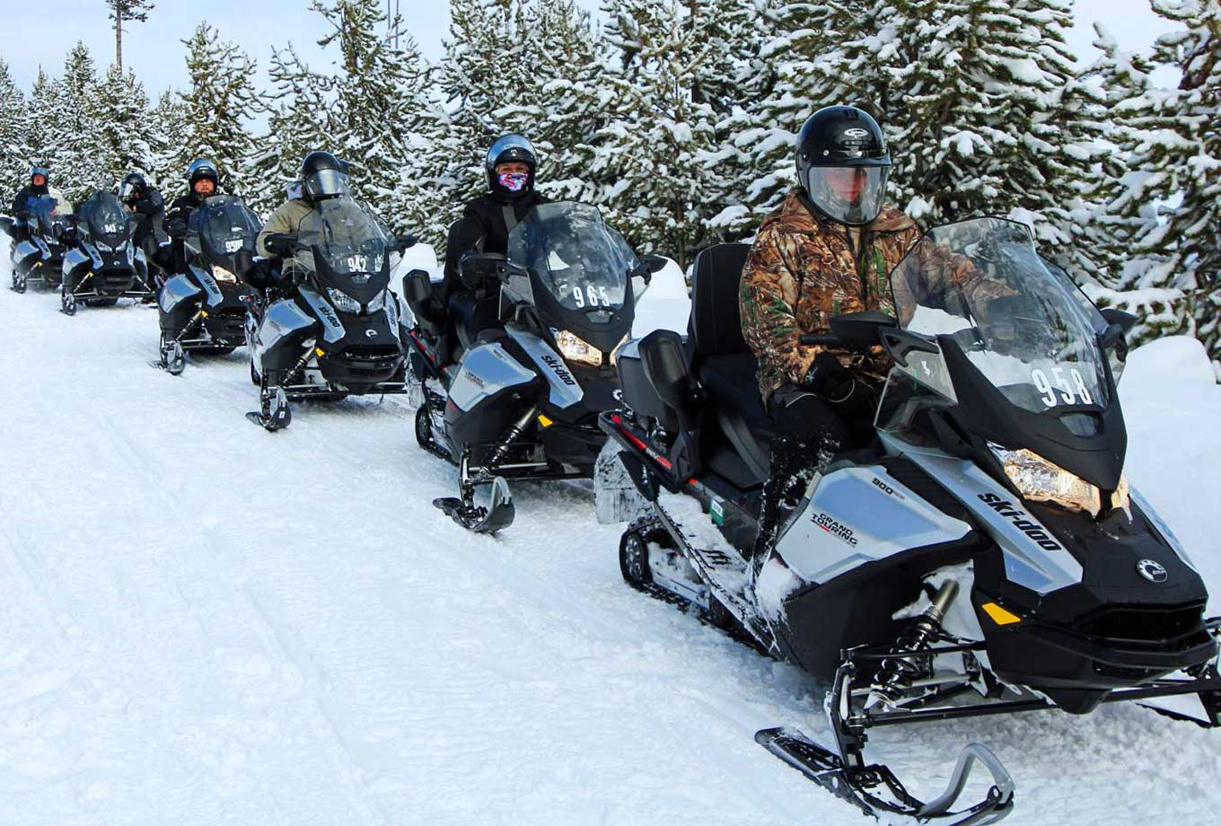 A group of snowmobile riders on a guided tour through Yellowstone National Park