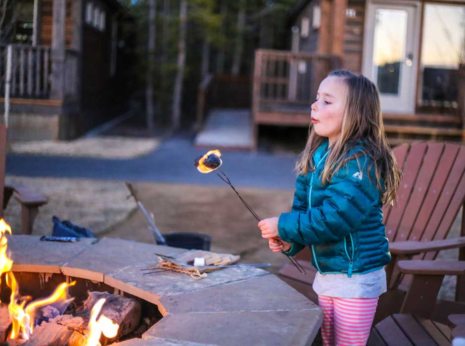 Little girl making S'mores at Explorer Cabins fire pits