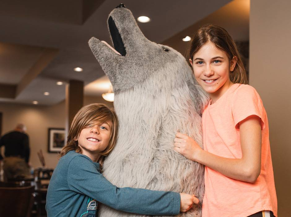 "Two kids posing with the Gray Wolf Inn & Suites mascot ""Caldera"""