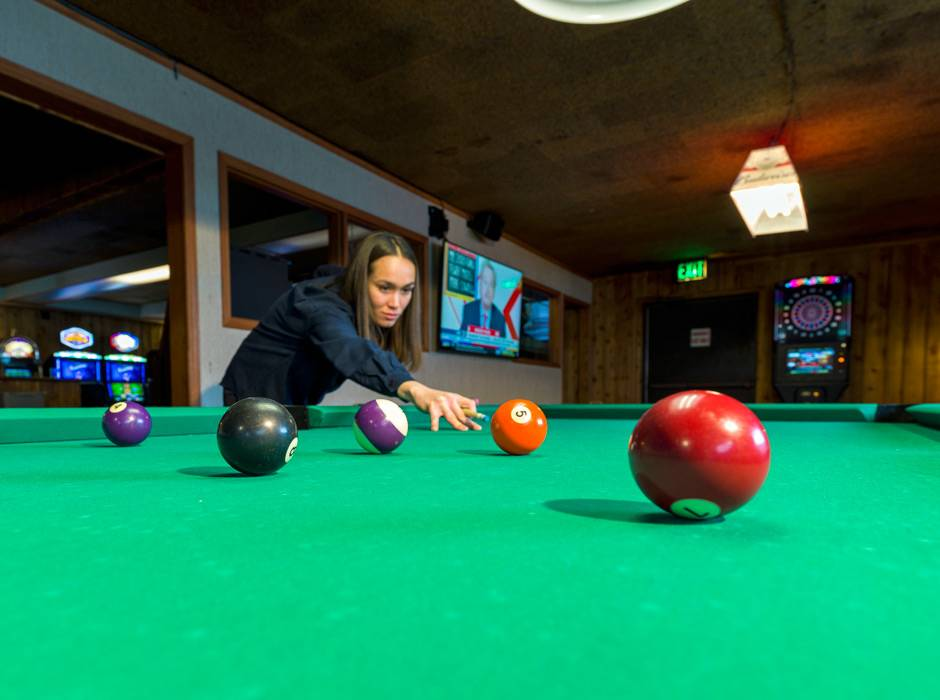 A guest shooting pool at the Ridgeline Hotel at Yellowstone