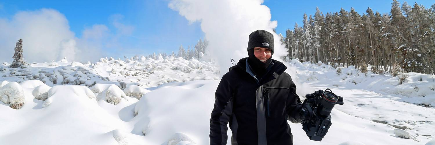 A photographer poses for a picture near a winter geyser in Yellowstone