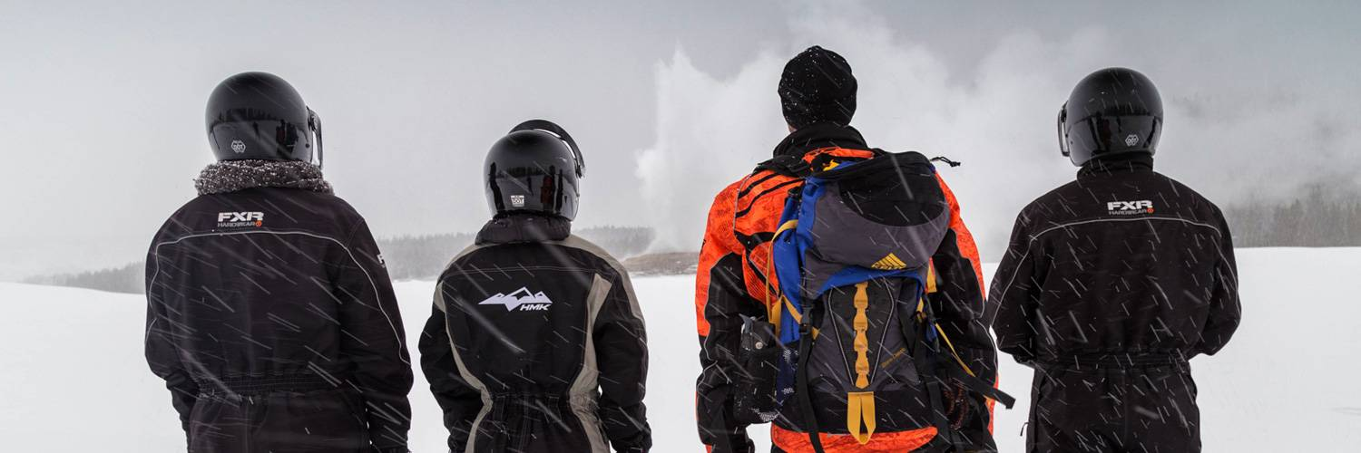 Yellowstone winter snowmobile riders watch an Old Faithful eruption