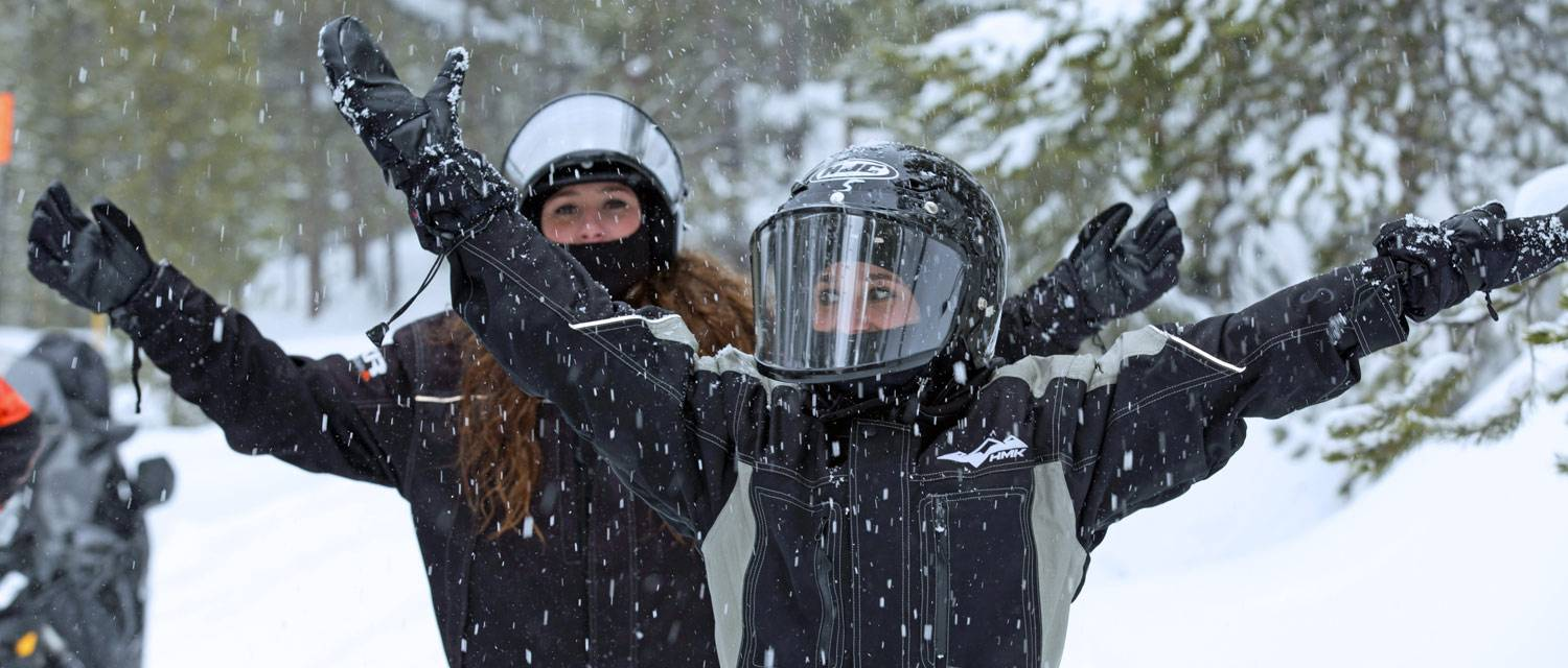 Two Yellowstone snowmobilers playing in the snow