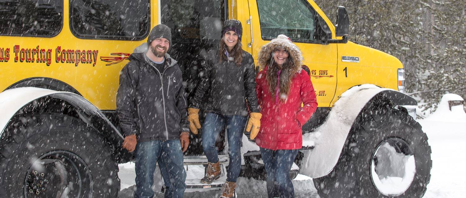 Man and two women standing outside winter snowcoach tour bus