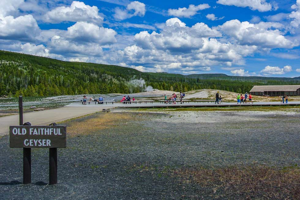 Old Faithful signage with people strolling behind