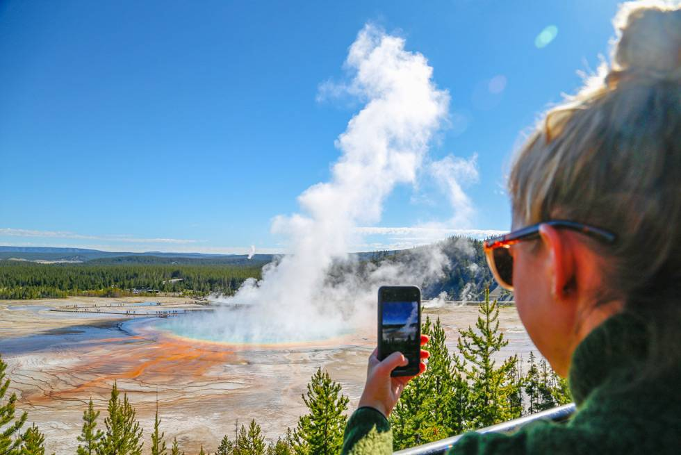 A Yellowstone visitor taking a cell photo of Grand Prismatic Spring