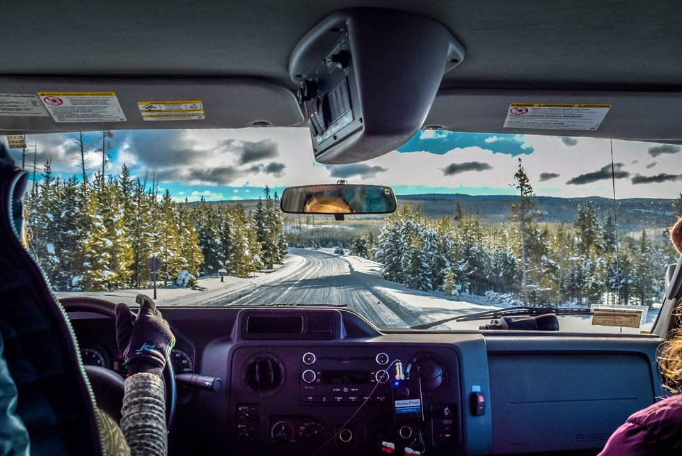 Stay warm and cozy on your snowcoach tour through the winter Yellowstone landscape.