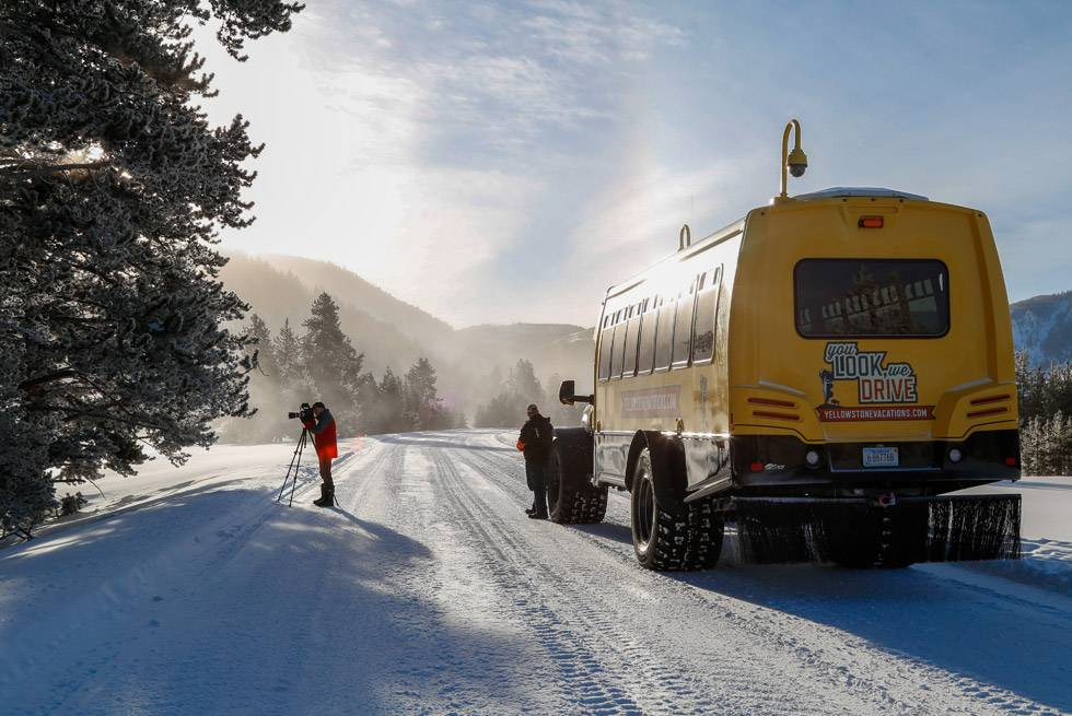 A photographer shooting the landscape on a Yellowstone Snowcoach Tour