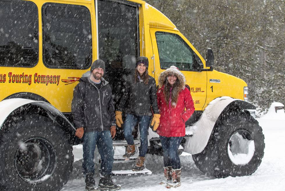 A group of Yellowstone snowcoach passengers pauses for a photo during their tour.