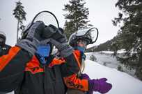 Kids using binoculars during a Yellowstone snowmobile tour