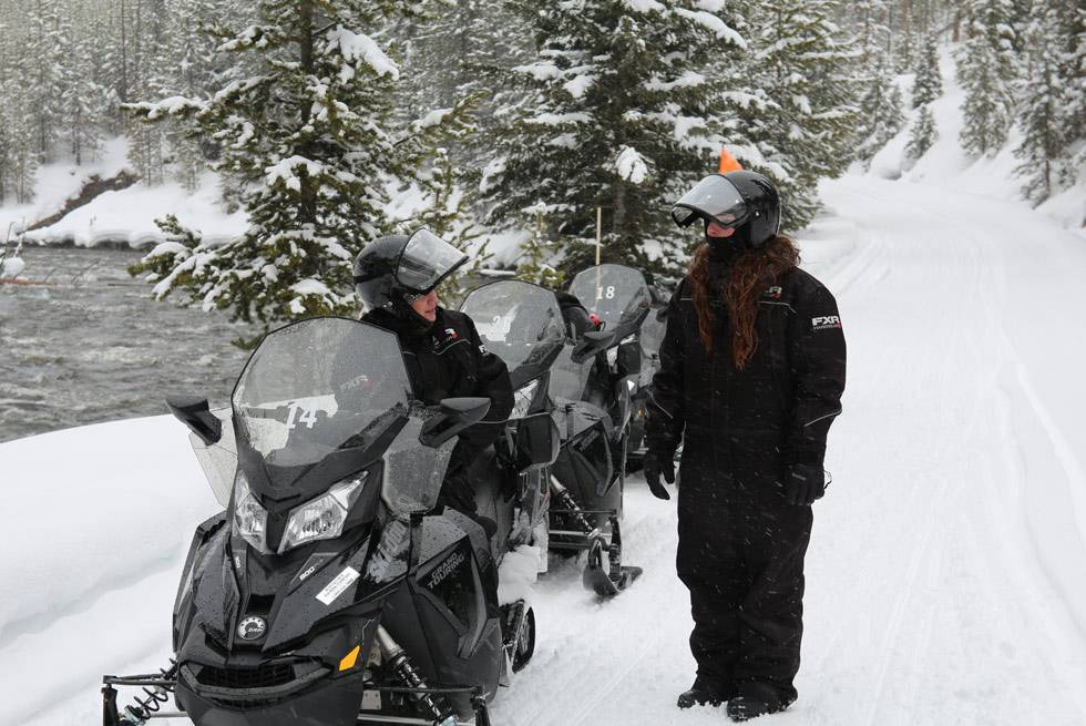 Snowmobilers take a quick break next to the Firehole River in Yellowstone Park.