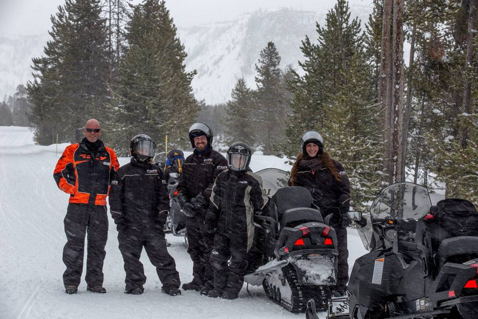 A Yellowstone snowmobiling group poses for a picture with their guide.