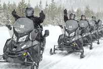 An excited group of snowmobilers gives an enthusiastic thumbs up for their Yellowstone tour.