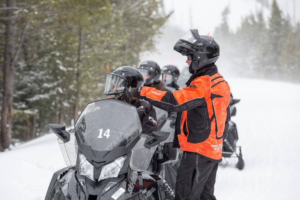 A Yellowstone snowmobile guide points out interesting features of the Park.