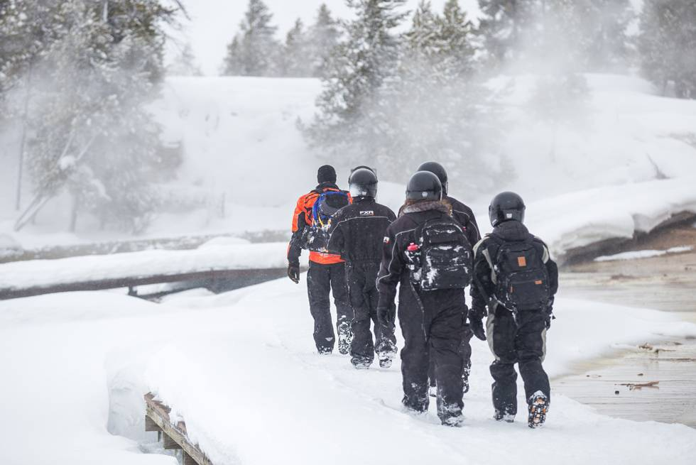 A snowmobile group stops at Midway Geyser Basin for a quick guided hike on the boardwalks.