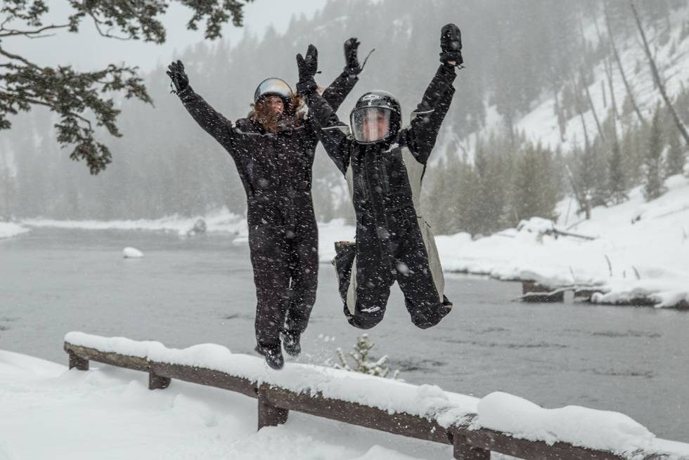 Yellowstone snowmobile riders jump for joy next to the Madison River.