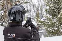 A Yellowstone snowmobiler pauses to take a quick cell phone photo.