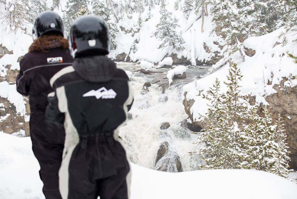 Two Yellowstone snowmobilers stop for a breathtaking winter photo of Firehole Falls