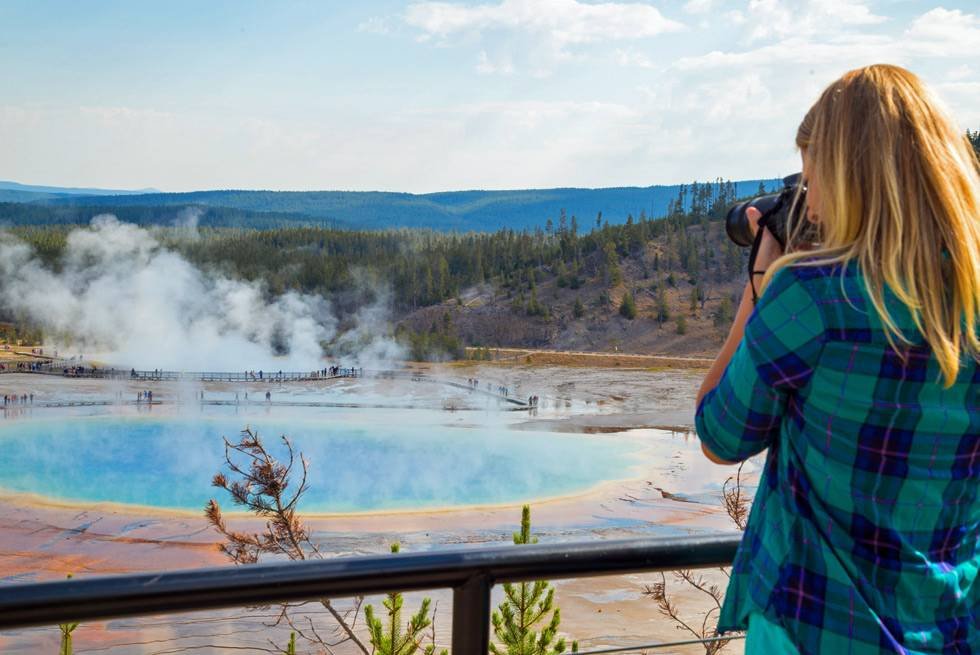 A summer bus tour passenger stops to take a photo of Grand Prismatic Springs