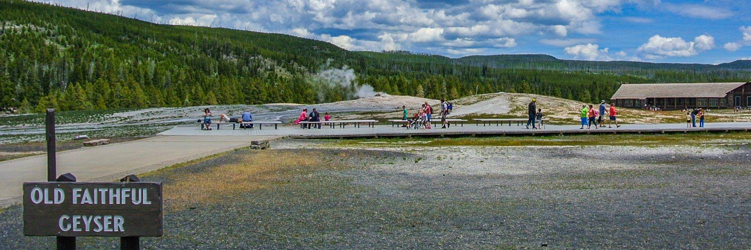 People walking by Old Faithful Geyser in Yellowstone National Park