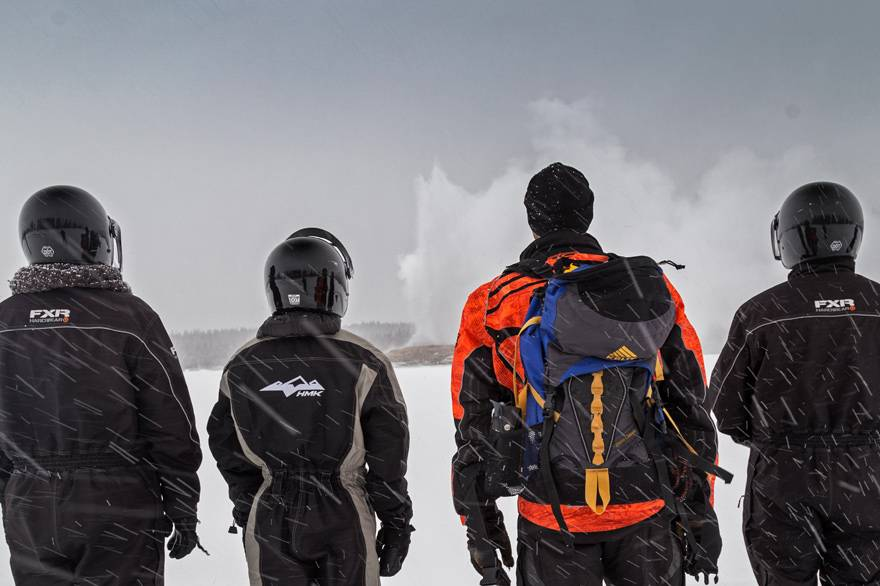 A group of snowmobilers watches Old Faithful erupt in winter
